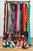 Dressing closet with colorful clothes and shoes nicely arranged on a rack. — Stock Photo