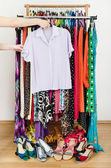 Woman hand picking up a purple shirt to wear. Summer dresses and sandals in a wardrobe. — Stock Photo