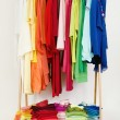 Wardrobe with summer clothes nicely arranged by colors. — Stock Photo #48440007