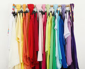 Close up on color coordinated clothes on hangers in a store. — Stock Photo