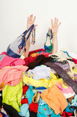 Man hands reaching out from a big pile of clothes and accessories. — Stock fotografie