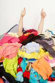 Man hands signing thumbs up reaching out from a big pile of clothes and accessories. — Stock Photo