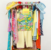 Rack with summer clothes and sale sign. — Stock Photo