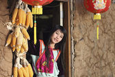 Lisu Hill tribe girl in traditional costume at door of earthen h — Stock Photo