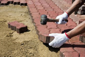 A worker laying red concrete paving blocks. — Stock Photo