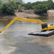 Excavator machine works at river — Stock Photo