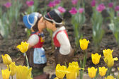 Two kissing dolls in tulip garden. — Stock Photo
