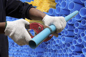 Worker cutting pvc pipe in construction site — Stock Photo
