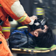 Rescue workers move hurt person with stretcher — Stock Photo #23563073