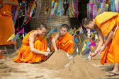Buddhist monk make sand chedi and pin traditional flags — Stockfoto