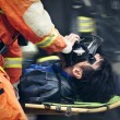 The rescue workers move hurt person with a stretcher - Stock Photo