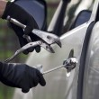 Car thief using a tool to break into a car. — Stock Photo