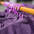 Row of cloth hangers with coats — Stock Photo