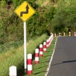 Stock Photo: Road sign warns of sharp turn on narrow road
