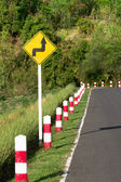 A road sign warns of a sharp turn on a narrow road — Stock Photo