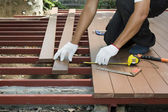 Worker installing wood floor for patio — Stock Photo