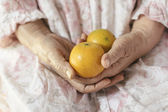 Chinese orange in old woman hands — Stock Photo