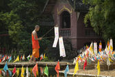 Buddhist monk with traditional flags — Stockfoto