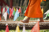 Buddhist Monk walk on bamboo bridge in the temple. — Stock Photo