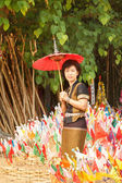 Woman with religion flag at temple in Songkran festival — Stockfoto