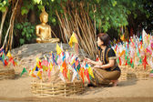 Woman pinned traditional flags on sand pagoda at temple — Stockfoto