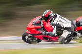 Racing bike rider leaning into a fast corner on track — Zdjęcie stockowe