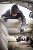 Thief stealing camera  from car — Stock Photo