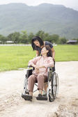 Young asian is taking care the senior woman with wheelchair in farm — Stock Photo