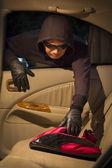 Thief stealing handbag  from car — Stock Photo