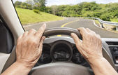 Senior woman driving a car slowly on highway — Stock Photo