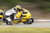 Motorcycle practice leaning into a fast corner on track — Stock Photo