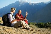 Tourist and monk in mountains — Stock Photo