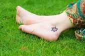 Six-pointed star tattoo on the girls foot — Stock Photo