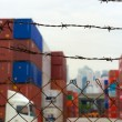Stock Photo: Seaport container terminal in Hongkong behind barbed wire