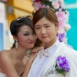 Couple Chinese girls posing in a wedding dress - Stock Photo