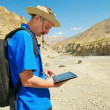 Tourist in mountains looking map on gadget — Stock Photo