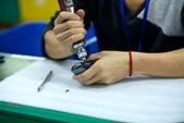Dělník s šroubovák a počítačové myši v jeho rukou na montážní lince v číně — Stock fotografie