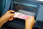 Chinese yuan issuing by ATM on hand — Stock Photo