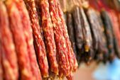 Many chinese sausage hanging on street market — Stock Photo