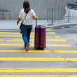 Girl with a suitcase crossing the street — Stock Photo