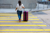 Girl with a suitcase crossing the street — Stok fotoğraf