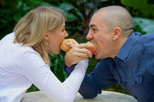 Husband and wife are competing eat applezz — Stock Photo
