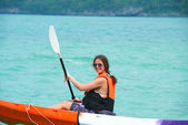 Pretty woman with a paddle kayaking on the sea — Stock Photo