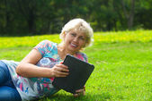 Woman with tablet lying on grass in park — Stock Photo