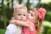 Beautiful little girl hugging and kissing the little handsome boy — Stock Photo
