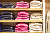 Stacked fashionable mens sweaters in retail place — Stock Photo