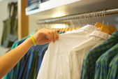 Buyer make choice t-shirt in a trendy store — Stock Photo