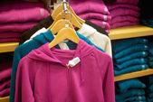 Womans sweats hanging in trendy boutique — Stock Photo
