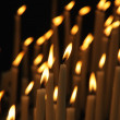 Stock Photo: Rows of firing candles in catholic church