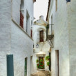 Small narrow street in spanish city with white houses — Stock Photo